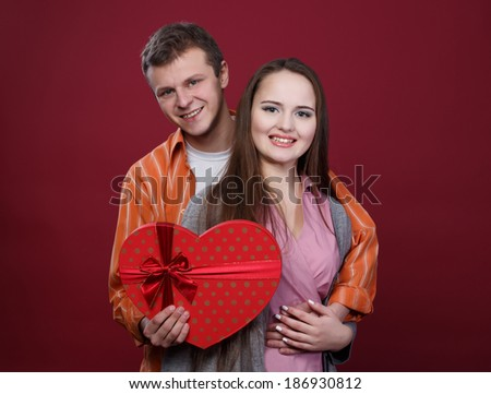 Boy and girl hold box in a shape of heart - stock photo