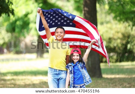 Boy and girl holding American flag in park