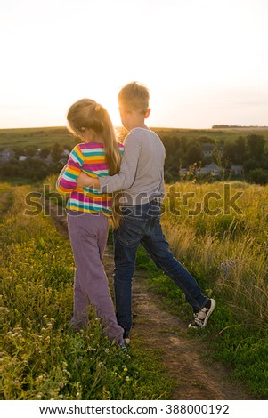 Boy and girl holding hands and walking along the road at sunset - stock photo