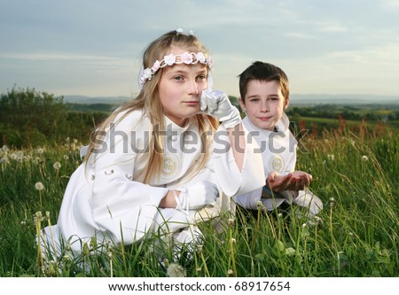 boy and girl in first holy communion on moody sky background, praying hands - stock photo