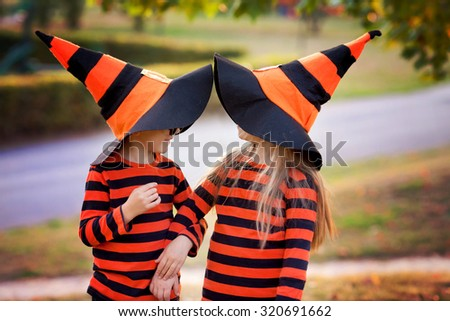 Boy and girl in the park in halloween costumes, having fun autumn time - stock photo