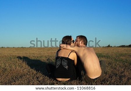 Boy and girl kissing in nature, grass and blue sky - stock photo