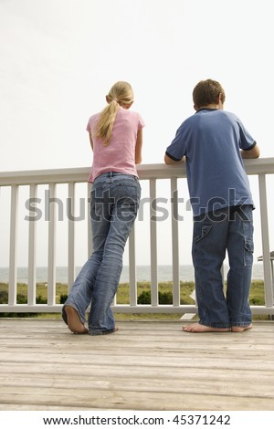 Boy and girl look over a porch railing at the beach. Vertical shot. - stock photo