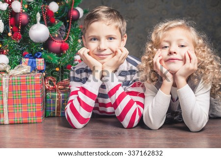 Boy and girl lying on the floor under the Christmas tree. Next to the gifts. They are looking at the camera, smiling, holding her head in her arms. Waiting for Christmas. Celebration. New Year. - stock photo