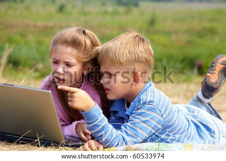 boy and girl lying on the lawn and do on your laptop