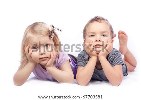 Boy and girl lying on white - stock photo
