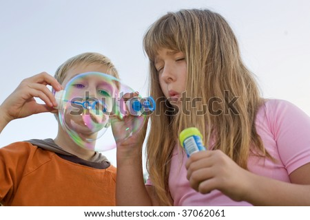 boy and girl make soap bubbles