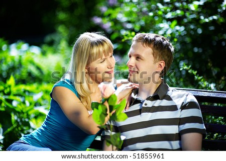 Boy and girl on a romantic date on a park bench