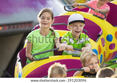 Boy and Girl on a thrilling roller coaster ride at an amusement park - stock photo