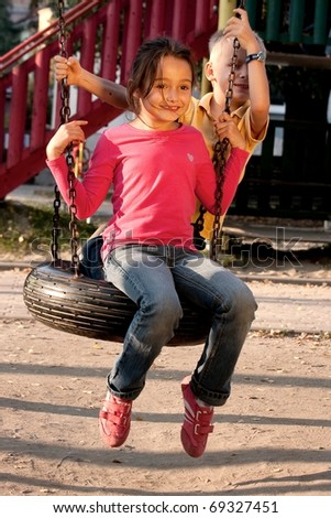 Boy and girl on swing playground outdoors - stock photo