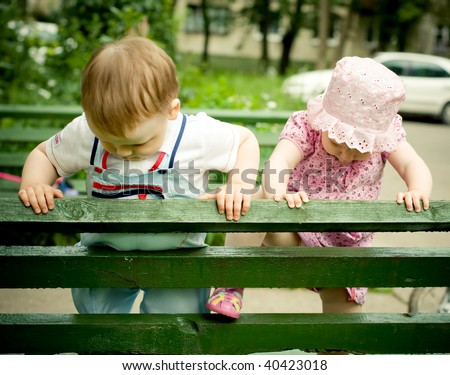 boy and girl on the bench in park - stock photo