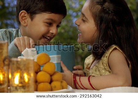 Boy and girl opening gifts on Diwali - stock photo