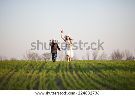 boy and girl playing on the field - stock photo