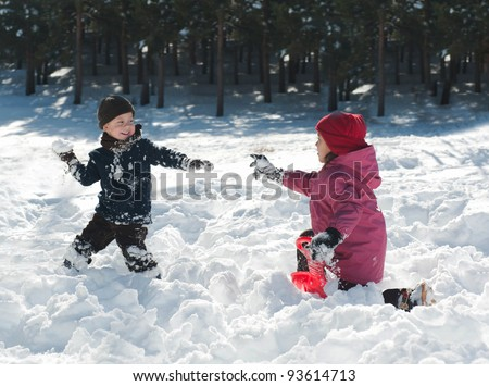 Boy and girl playing snowballs - stock photo