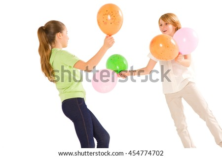 boy and girl playing with balloons isolated on white background - stock photo