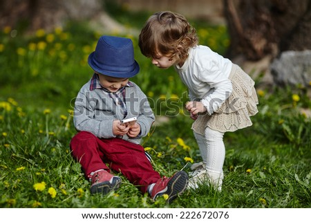 boy and girl playing with mobile phone - stock photo