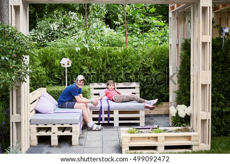 Boy and girl relax in wooden alcove made of pallets outdoor in summer park.