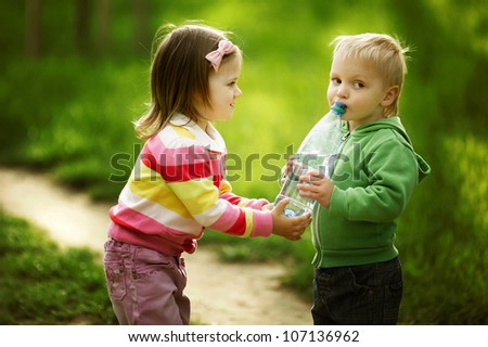 boy and girl sharing bottle of water - stock photo