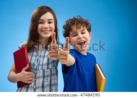 Boy and girl showing thumbs up sign