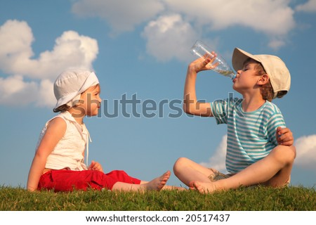Boy and girl sit on grass and drink from bottle - stock photo