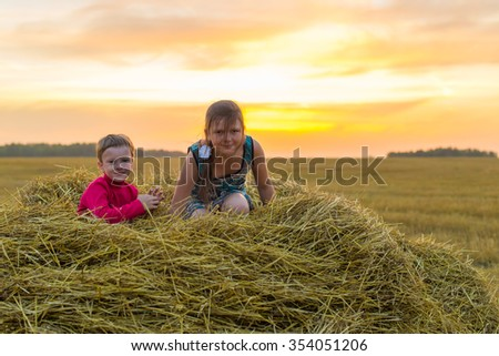 Boy and girl sitting on a stack of straw yellow smiling on the background of the setting, the rising sun in the clouds - stock photo