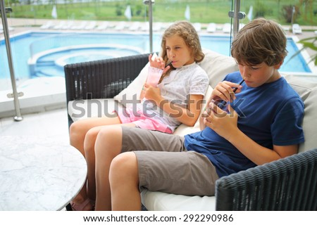 Boy and girl sitting on the couch and drinking cocktails on the terrace, focus on boy - stock photo
