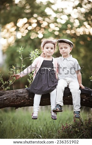 boy and girl sitting on tree - stock photo