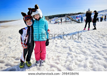 Boy and girl skiing in mountains. School agedkids  with helmet, goggles, poles. Ski race for children. Winter sport for family. Kids ski lesson in alpine school. Little skier racing in snow - stock photo