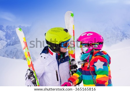Boy and girl skiing in mountains. Toddler kid and teenager with helmet, goggles, poles. Ski race for children. Winter sport for family. Kids ski lesson in alpine school. Little skier racing in snow - stock photo