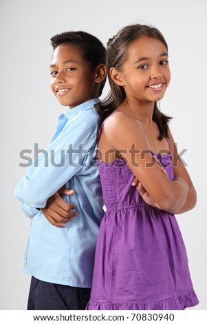 Boy and girl standing back to back smiling - stock photo