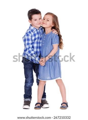boy and girl standing  cheek to cheek full length portrait - stock photo