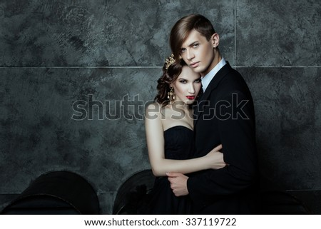 Boy and girl standing in an embrace, her crown on his head. Fashionable and stylish couple for a fashion magazine. - stock photo