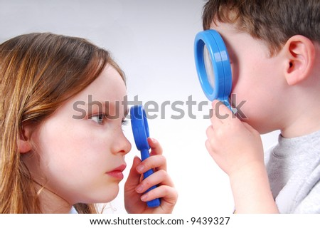 Boy and Girl Studying One Another with Magnifying Glasses - stock photo