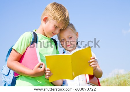 boy and girl together read the book about the school