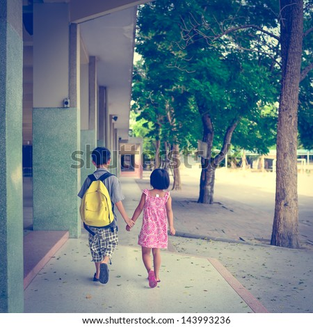 boy and girl walking in the school with holding their hands - stock photo