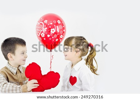 boy and girl watch and smiling,best focus of the boy's eye, hair, shirt and heart, soft focus girls