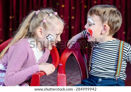 Boy and Girl Wearing Clown Make Up Sitting Side by Side and Sticking Tongues Out at Each Other - stock photo
