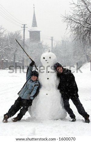 Boy and girl with a snowman - stock photo