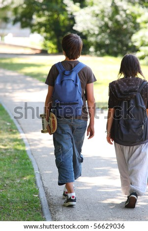 Boy and girl with backpacks having a walk - stock photo