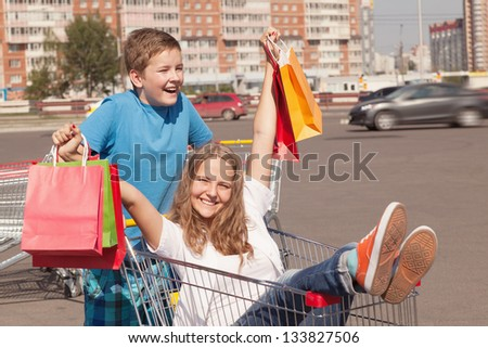 boy and girl  with shopping trolley full of purchases in the street - stock photo