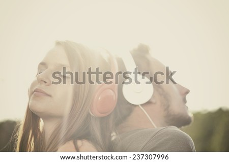Boy and girll listening to music on headphones - stock photo