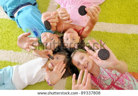 boy and girls playing with cookies - stock photo