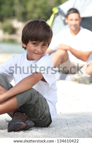 Boy and his Dad camping - stock photo
