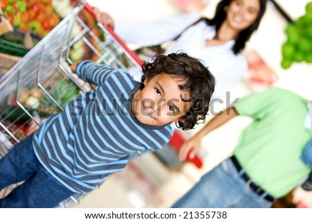 boy and his family shopping at the supermarket - stock photo