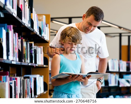Boy and his father in library choosing books - stock photo