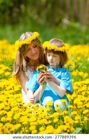 Boy and his Mother Sitting in a Dandelion Field - stock photo