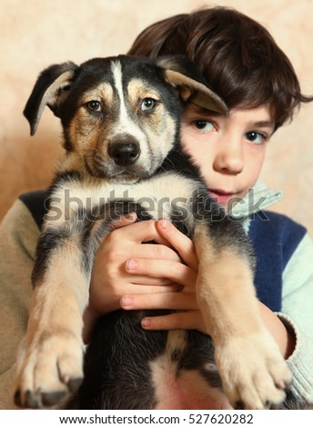 boy and little puppy look