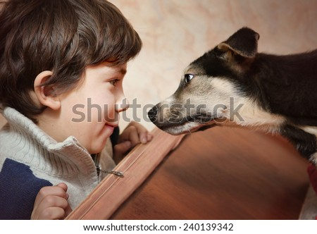 boy and little puppy look to each other - stock photo