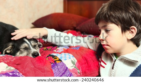 boy and little puppy sleeping on the bed