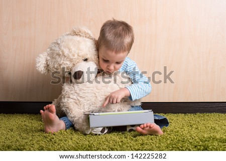 Boy and teddy bear with tablet computer - stock photo